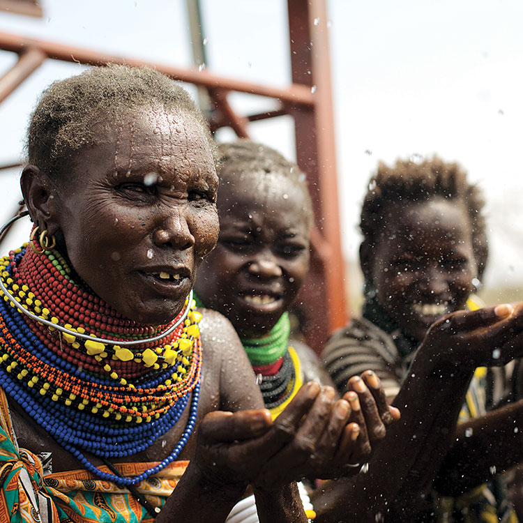 Regina Arii and two other women hold out their hands with joy and thanks for clean water in Lodwar, Kenya.