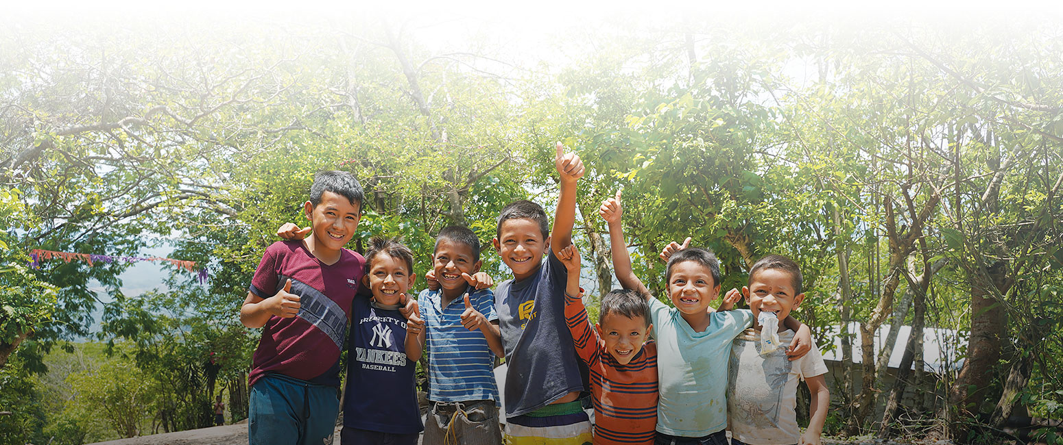 A group on young Guatemalan children smile and wave.