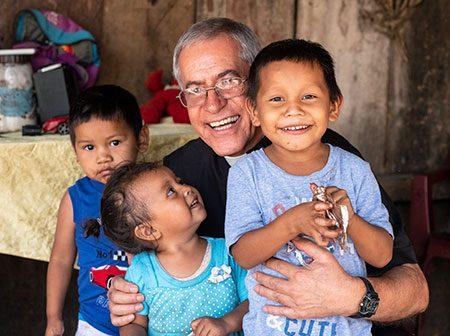 A Catholic priest kneels with three small Guatemalan children.