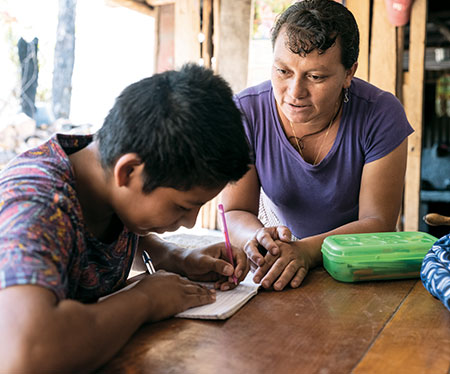 Umbelina helps her foster son, Jose, with his homework.