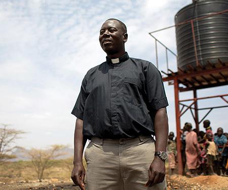 Father Fabian Hevi stands in front of water kiosk in Mokine, Kenya