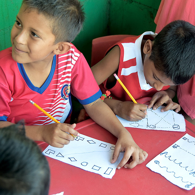 School boys sit with pencils and paper to do an educational activity at a feeding center.