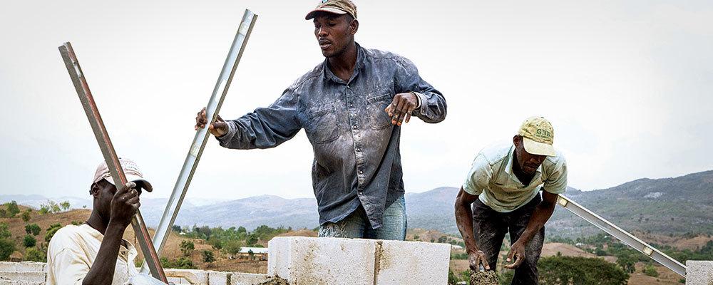 Three men work to build a concrete block house wall in Haiti.
