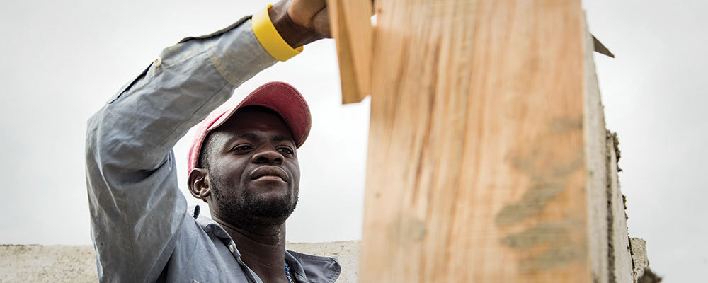 A construction worker plasters the wall of a home he's building in Haiti.