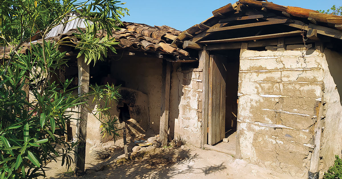 Severe damage is visible on the exterior mud walls of a Nicaraguan house.