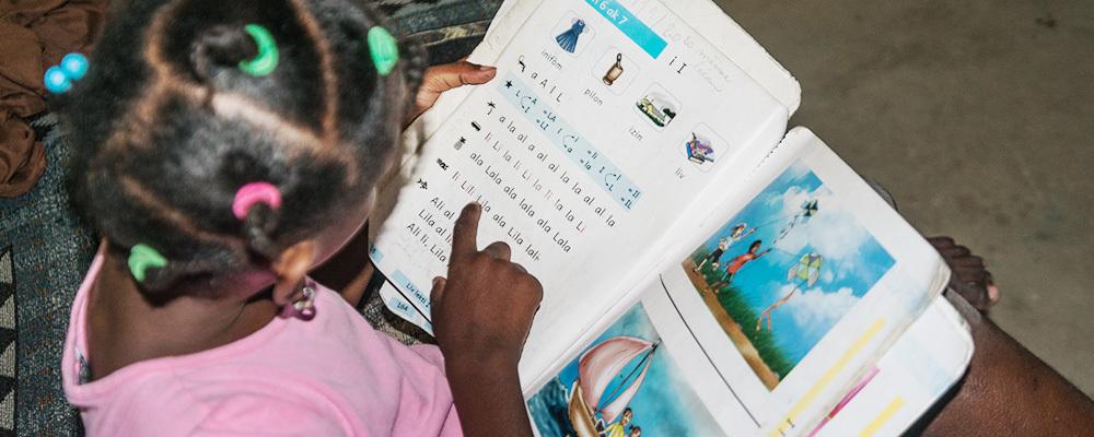 A little girl studies under solar-powered lights.