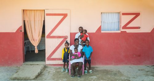 A Haitian family sits in front of their Kobonal house.